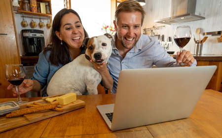 COVID-19 Stay connected. Happy couple and pet dog video calling friends using laptop at home. Man and woman online chatting with family celebrating easing of coronavirus restrictions. Hope concept. Banco de Imagens