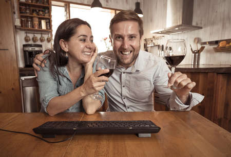 Screen view of Happy couple video calling friends and family using laptop at home. Man and woman online chatting and cheering with wine celebrating easing of coronavirus restrictions. Hope concept. Banco de Imagens - 157271858