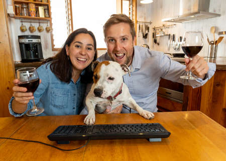 Screen view of Happy couple and pet dog video calling friends using laptop at home. Man and woman online chatting and cheering with wine celebrating easing of coronavirus restrictions. Hope concept.