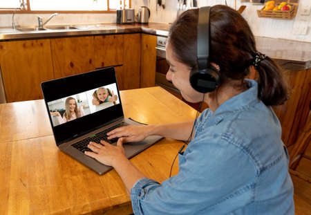 COVID-19 Online Education. Primary teacher and pupil interacting in live video lesson. Woman tutor with headset and laptop working remotely from home online teaching child student in video conference.
