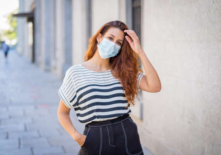 Young attractive red haired woman with protective medical mask in city street. Outdoors portrait of woman wearing face mask. Positive image of New Normal life after COVID-19 and Stop the virus spread.