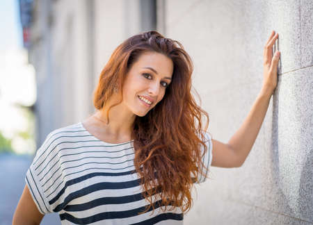 Outdoors close up portrait of young attractive woman with curly red hair and sensual smile. Female model posing with natural beauty urban background. Real People, beauty care, fashion and lifestyle.