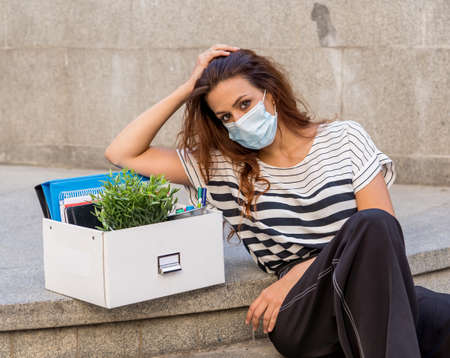 Sad businesswoman in medical protective mask in business district with box of office staff feeling depressed due to job loss. Coronavirus job cuts, COVID-19 unemployment and economic crisis concept. Stok Fotoğraf