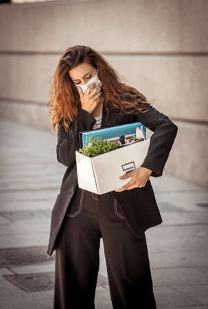 Depressed business woman with face mask outside office with personal staff box feeling hopeless after being fired from work. Coronavirus job losses, lay off and COVID-19 Outbreak impact on employment.