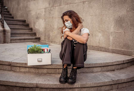 Sad businesswoman in medical protective mask in business district with box of office staff feeling depressed due to job loss. Coronavirus job cuts, COVID-19 unemployment and economic crisis concept.
