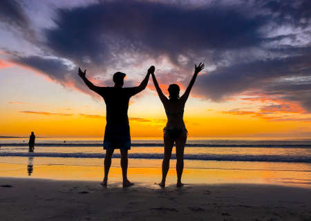 Couple in love holding hands feeling free during honeymoon at spectacular beach sunset. Man and woman silhouette celebrating love freedom and health. Romantic escapes holidays and wellness concept.