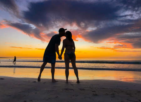 Couple in love silhouette kissing feeling free during honeymoon at beach sunset. Man and woman silhouette celebrating love freedom and health. Romantic escapes holidays and wellness concept. Stok Fotoğraf
