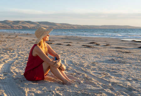 Happy attractive Mature woman in red dress enjoying outdoors and freedom on the beach, open arms outstretched in hope after coronavirus quarantine eased. Back to life, outdoors and new normal concept.