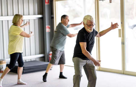 Group of seniors in Tai Chi class exercising in an active retirement lifestyle. Mental and physical health benefits of exercise and fitness in elderly people. Senior health care and wellbeing concept. Banco de Imagens - 157047469
