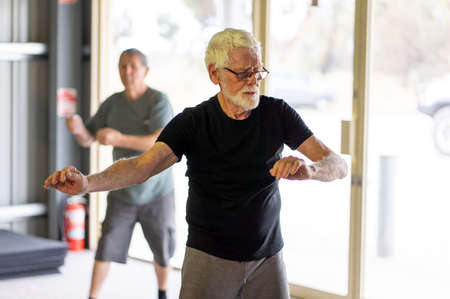 Group of seniors in Tai Chi class exercising in an active retirement lifestyle. Mental and physical health benefits of exercise and fitness in elderly people. Senior health care and wellbeing concept. Banco de Imagens - 157033450