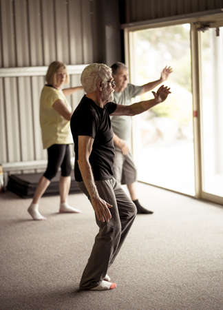 Group of seniors in Tai Chi class exercising in an active retirement lifestyle. Mental and physical health benefits of exercise and fitness in elderly people. Senior health care and wellbeing concept. Banco de Imagens - 157033096