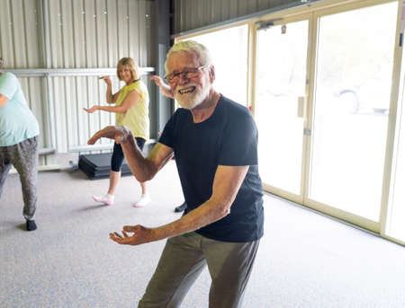Group of seniors in Tai Chi class exercising in an active retirement lifestyle. Mental and physical health benefits of exercise and fitness in elderly people. Senior health care and wellbeing concept. Banco de Imagens - 157047703