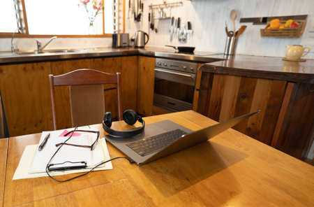 COVID-19 and working from home concept. Conceptual image with no people of workspace with laptop, headphones, glasses and paperwork on kitchen table in coronavirus pandemic and new normal. Banco de Imagens