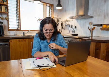 Stressed business woman working from home on laptop looking worried, tired and overwhelmed. Exhausted female working remotely during social distancing. Mental health and coronavirus lockdown. Banco de Imagens - 157048080