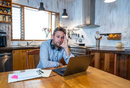 Stressed business man on laptop working from home looking worried, tired and overwhelmed. Exhausted entrepreneur working remotely during social distancing. Mental health and coronavirus lockdown. Banco de Imagens - 157047904