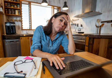 Stressed business woman working from home on laptop looking worried, tired and overwhelmed. Exhausted female working remotely during social distancing. Mental health and coronavirus lockdown.