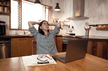 Stressed business woman working from home on laptop looking worried, tired and overwhelmed. Exhausted female working remotely during social distancing. Mental health and coronavirus lockdown. Banco de Imagens - 157047944