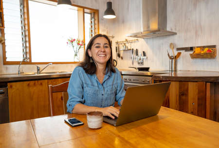 Happy successful woman on laptop working from home. Freelancer or employee in video conference virtual meeting working remotely in COVID-19 lockdown, social distancing and New normal concept. Banco de Imagens