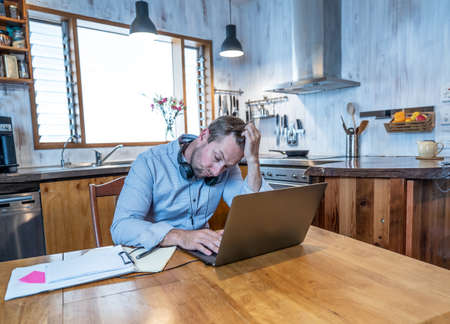 Stressed business man on laptop working from home looking worried, tired and overwhelmed. Exhausted entrepreneur working remotely during social distancing. Mental health and coronavirus lockdown.