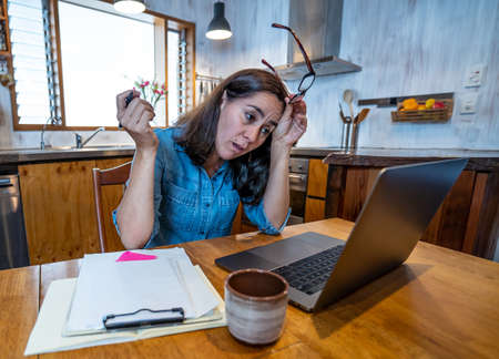 Stressed business woman working from home on laptop looking worried, tired and overwhelmed. Exhausted female working remotely during social distancing. Mental health and coronavirus lockdown. Banco de Imagens - 157047693