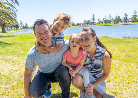 Happy family portrait of mother, father, son and daughter having fun together in the park. Boy and little girl enjoying time with their parents. Positive emotion, parenting and childhood concept.