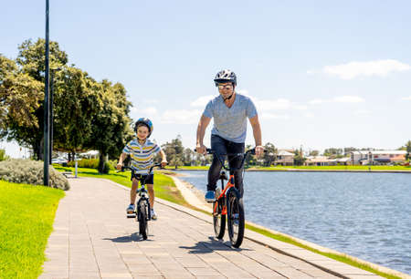 Happy Father and son riding their bicycles by the lake. Father and son having fun together on their bikes in the park. Happy family, outdoors activities, childhood and parenting concept.