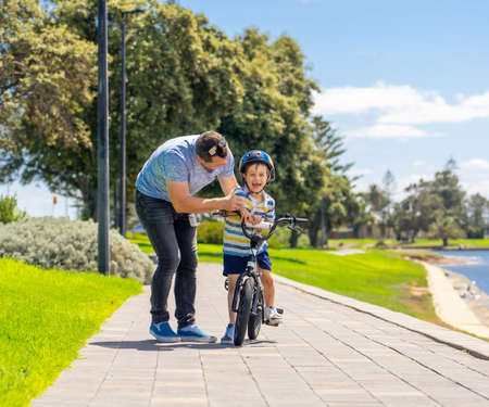 Boy learning to ride a bicycle with his father in the park by the lake. Father and son having fun together on the bikes. Happy family, outdoors activities, childhood and parenting concept. Banco de Imagens