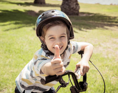 Cute cheerful boy with helmet on his new bike by the lake at the park. Lifestyle portrait of happy kid on his bicycle. Outdoor activities, vacations, happy childhood and back to normal concept. Banco de Imagens - 157019315