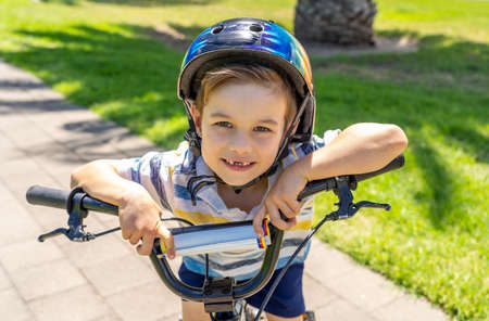 Cute cheerful boy with helmet on his new bike by the lake at the park. Lifestyle portrait of happy kid on his bicycle. Outdoor activities, vacations, happy childhood and back to normal concept. Banco de Imagens