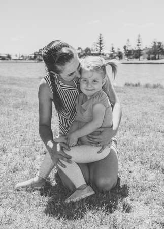 Positive portrait of mother and daughter having fun together by the lake. Cute little girl with mum in the park. Love, Family time, motherhood, childhood and outdoors concept.
