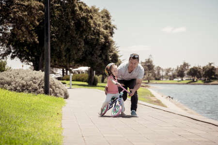 Little girl learning to ride a bicycle with his father in the park by the lake. Father and daughter bonding and having fun together. Happy family, outdoors activities, childhood and parenting concept.