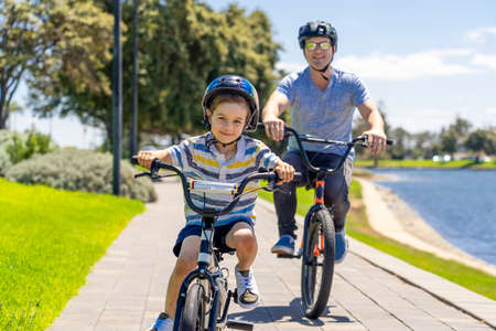 Happy Father and son riding their bicycles by the lake. Father and son having fun together on their bikes in the park. Happy family, outdoors activities, childhood and parenting concept. Banco de Imagens - 157019434