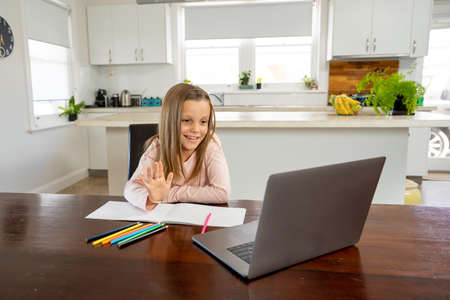 Happy Schoolgirl on laptop watching online lesson learning remotely at home in self-isolation. Education, Quarantines and Schools reopening or shutting down in-person learning due to COVID-19.