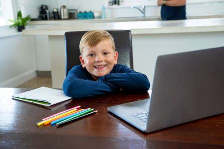 Happy Schoolboy on laptop watching online lesson learning remotely at home in self-isolation. Education, Quarantines and Schools reopening or shutting down in-person learning due to COVID-19 Pandemic.
