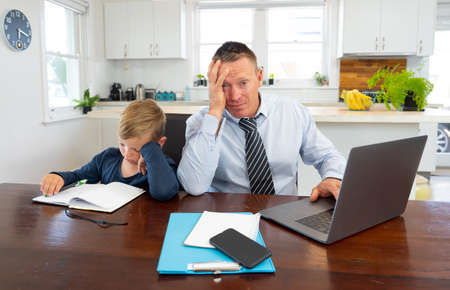 Stressed parent trying to cope with remote work and homeschooling. Man working from home while son child wants his attention. COVID-19 lockdown, quarantine, online learning and work from home concept.