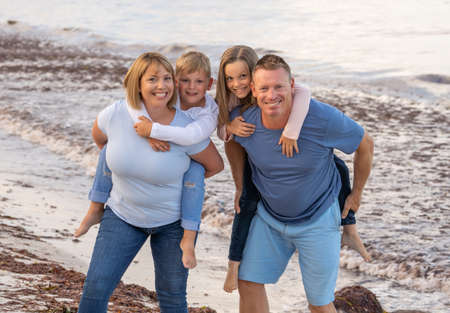 Outdoors portrait of a happy family of four members, mom, dad, and children boy and girl, embracing and having fun together at the beach. Happy moments, vacations and holiday portrait concept.