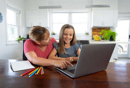 Mother helping child daughter studying at home in self-isolation or quarantine. Education, Home schooling, Remote learning and School closures due to Coronavirus second wave concept.