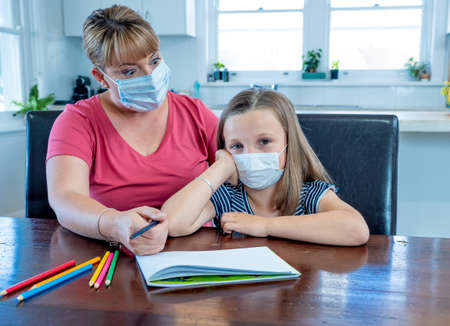 Stressed Mother helping bored daughter studying online lesson at home. Parent and child with face mask homeschooling during second lockdown, self isolation or School closures due to COVID-19 Outbreak. Banco de Imagens