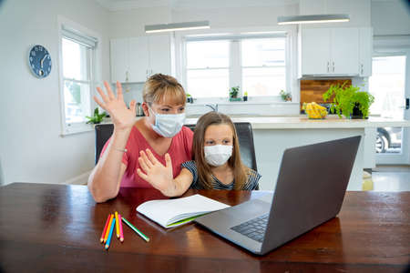 Mother and child daughter with face mask in self-isolation or quarantine talking to teacher online. Education, Home schooling, Remote learning and School closures due to Coronavirus second wave.