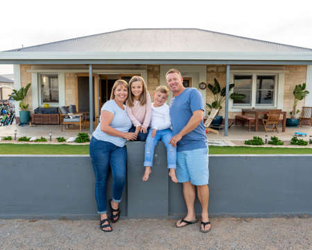 Outdoors portrait of a happy family of four smiling in front of new dream home or vacation rental house. Mom, dad, and children boy and girl, embracing and having fun together enjoying holiday villa.