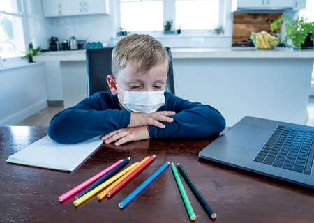 School boy with face mask watching virtual lesson in online education feeling bored and depressed at home in self-isolation. Remote learning and closed schools due to COVID-19 outbreak second wave.
