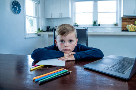 Sad school boy watching virtual lesson in online education classes feeling bored and depressed at home in self-isolation. COVID-19 second wave, quarantine, school closures and remote learning concept. Banco de Imagens