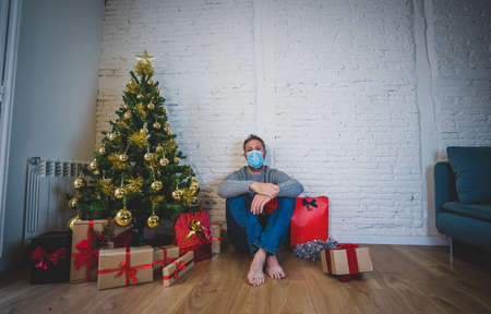 Sad man with mask home alone in self isolation at christmas feeling depressed mourning and missing family and friends. COVID-19 Lockdown and quarantine during winter holidays and mental health. Banco de Imagens