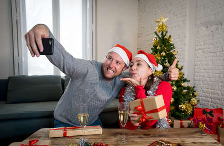 Happy couple video calling friends with mobile cell phone celebrating Virtual christmas and New year in lockdown. Virtual celebrations, social distancing during winter holidays due to COVID-19.