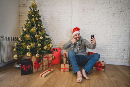 Happy man using smart phone home alone in lockdown celebrating virtual christmas video calling family and friend. Virtual holiday gathering online due to coronavirus New normal and social distancing.
