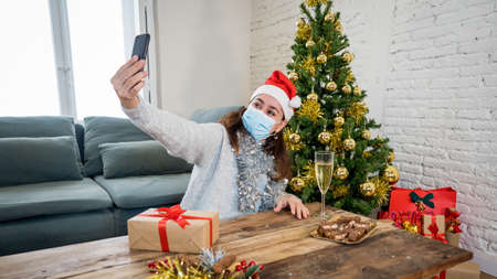 Happy woman with face mask home alone in lockdown using smart mobile cell phone, celebrating Virtual christmas video calling family and friends. COVID-19 Virtual holidays and online social gathering. Banco de Imagens