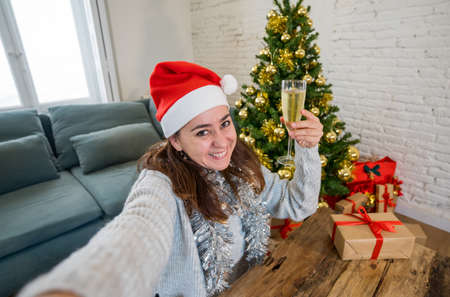 Happy woman in quarantine celebrating virtual christmas video calling family and friend on smart mobile cell phone. Virtual holiday gathering online due to coronavirus quarantine social distancing.