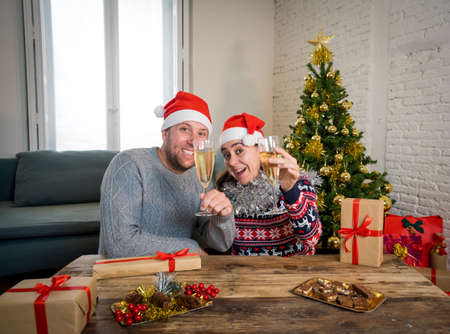 Happy couple celebrating Virtual christmas and new year in lockdown. Webcam view portrait of couple on video call or virtual christmas party. Online celebrations and COVID-19 social distancing.