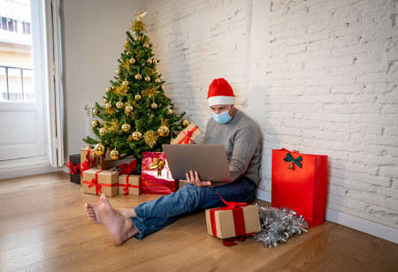 Happy man with face mask home alone in lockdown celebrating virtual christmas video calling family and friend. Virtual holiday gathering online due to coronavirus New normal and social distancing.
