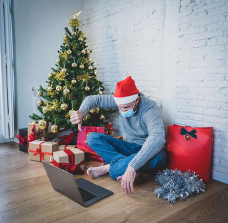 Sad man with face mask video calling family and friends feeling depressed home alone in lockdown at christmas. COVID-19 virtual holiday celebrations, social distancing, lockdown and mental health. Stock Photo